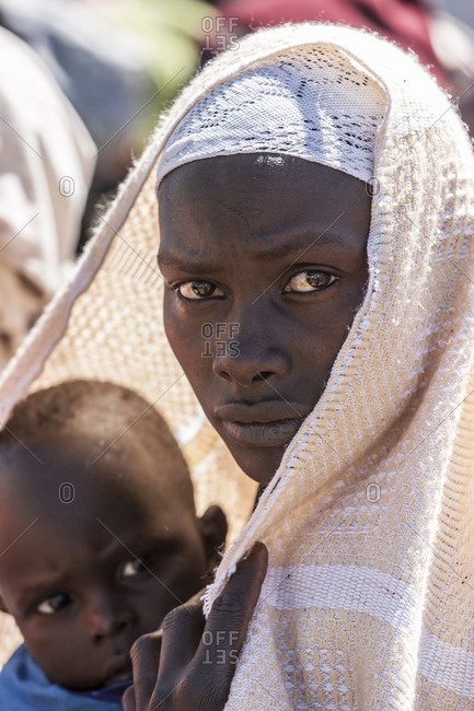 Woman and child wait in a line for medical aid in Kenya