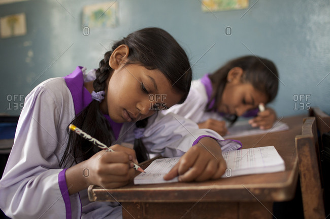 Young Pakistani girls working in workbooks during class