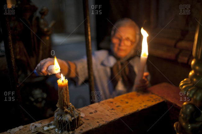 Orthodox Christian woman lights candles at the Church of the Holy Sepulchre