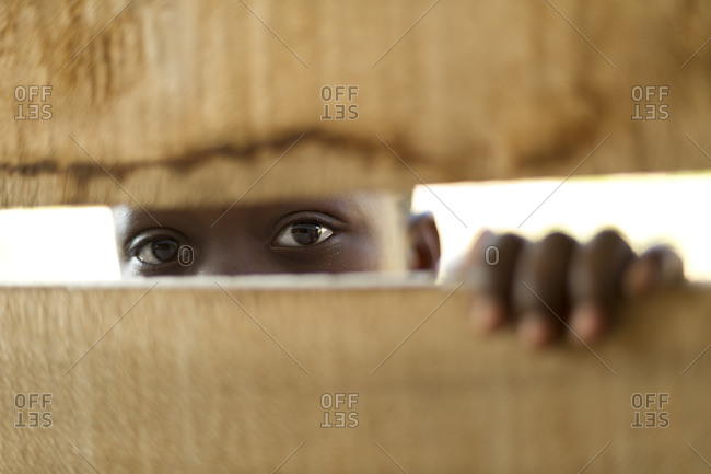Child peeks through slats of wooden church building in Rwanda