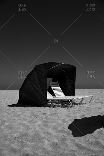 Beach tent with two chairs on seashore