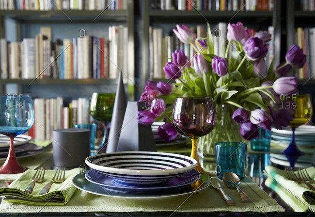 Laid table with bouquet of purple tulips