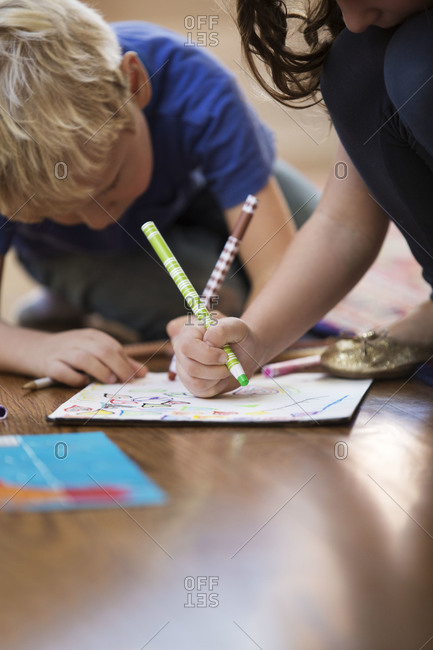 Kids sitting on floor at home and drawing