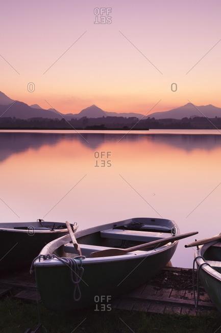 Rowing boats on Hopfensee Lake at sunset, near Fussen, Allgau, Allgau Alps, Bavaria, Germany, Europe