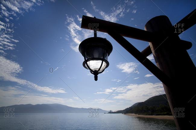 Lamp hanging on wooden post on seashore