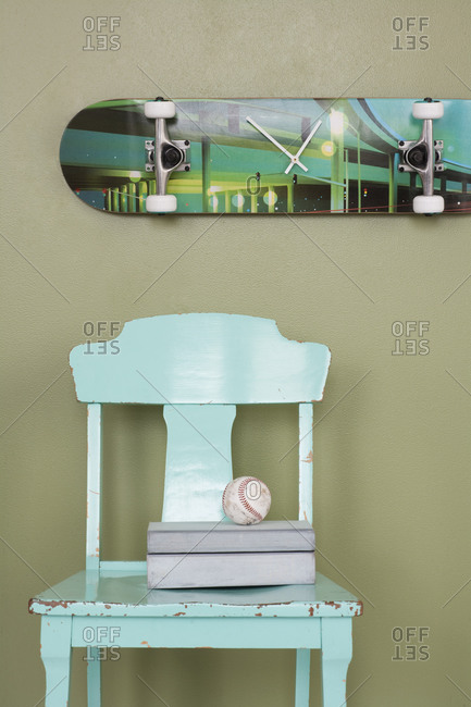 Box and baseball ball on chair and a skateboard as a clock hanging on the wall