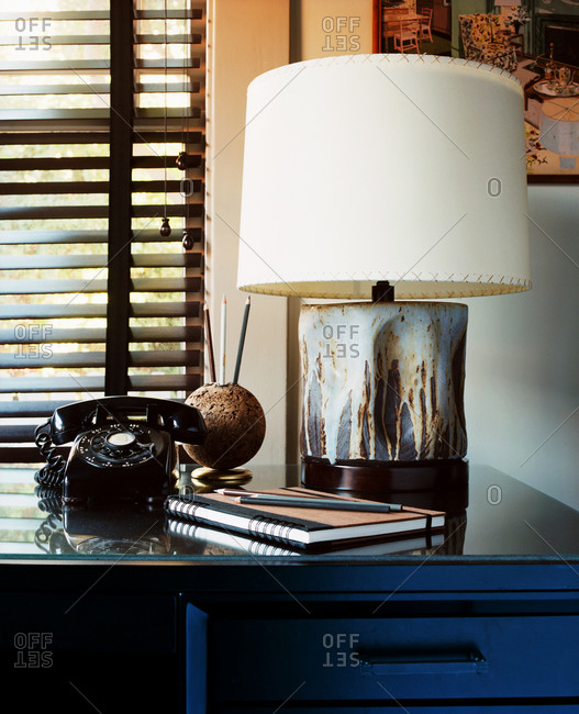 Still life of rotary dial phone, lamp and notebook on drawer