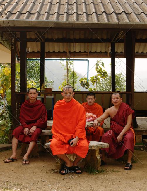 Thailand - January 5, 2014: Buddhist monks sitting outdoors