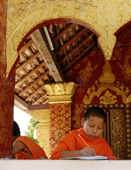 Luang Prabang, Laos - January 12, 2014: Novice Buddhist monk writing at a temple