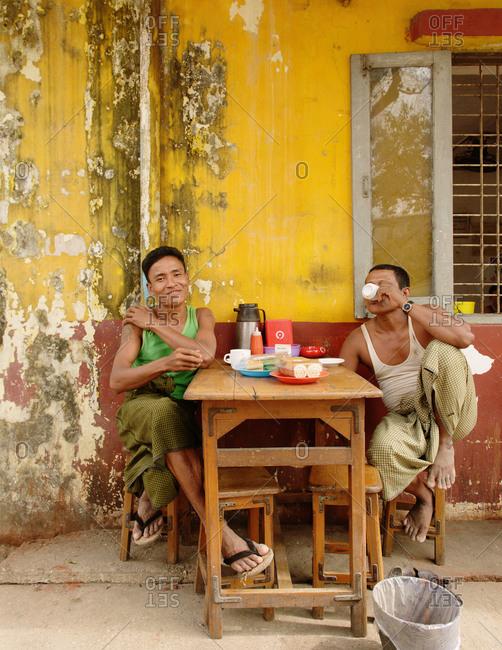 Yangon, Burma - December 11, 2013: Two men drinking coffee outdoors