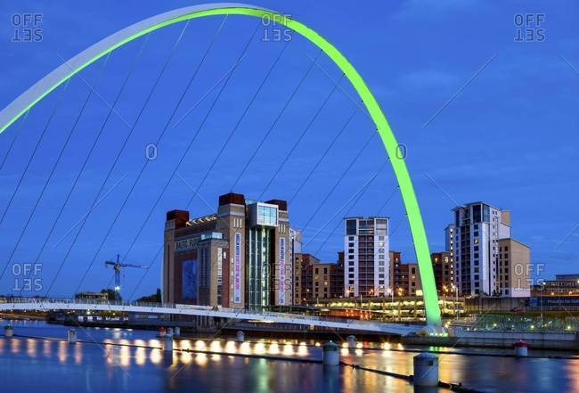 View along the Quayside at night showing the Baltic Centre for Contemporary Arts framed by the floodlit Gateshead Millennium Bridge, Newcastle-upon-Tyne, England.
