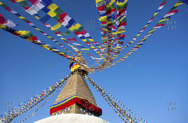 Bodhnath Stupa (Boudhanth) (Boudha), one of the holiest Buddhist sites in Kathmandu, UNESCO World Heritage Site, with colorful prayer flags against clear blue sky, Kathmandu, Nepal, Asia