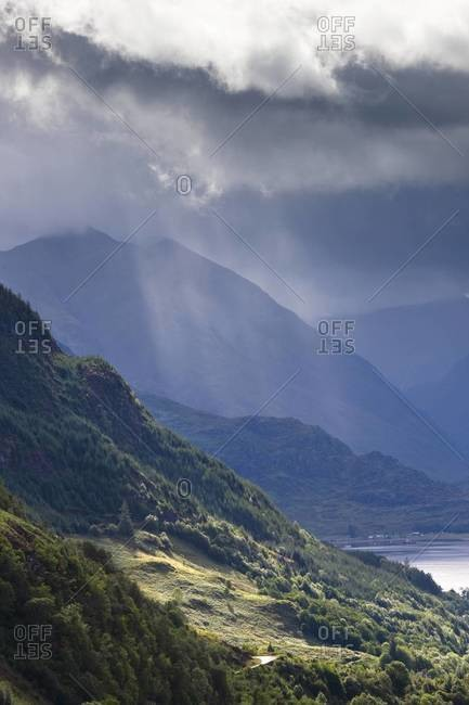 View from Carr Brae towards head of Loch Duich and Five Sisters of Kintail with sunlight bursting through sky. Scotland