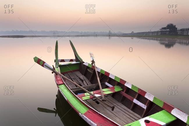 Traditional rowing boat moored on the edge of flat calm Taungthaman Lake at dawn with the  of the sky reflecting in the calm water, close to the famous U Bein teak bridge, near Mandalay, Myanmar (Burma), Asia