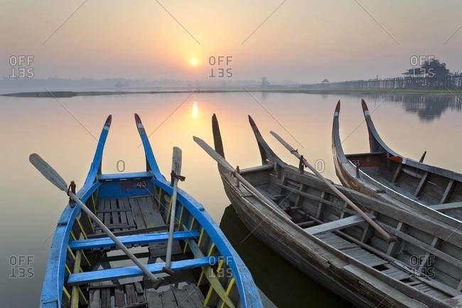 Traditional rowing boats moored on the edge of flat calm Taungthaman Lake at dawn with the  of the sky reflecting in the calm water, close to the famous U Bein teak bridge, near Mandalay, Myanmar (Burma), Asia