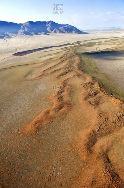 Aerial view from hot air balloon over magnificent desert landscape of sand dunes, mountains and Fairy Circles, Namib Rand game reserve, Namib Naukluft Park, Namibia, Africa