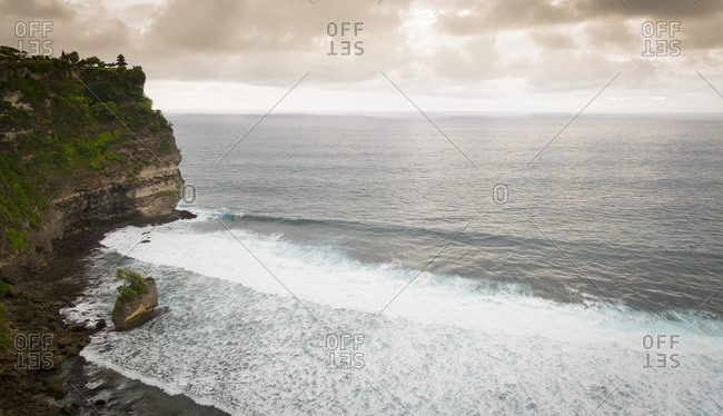 The Pura Luhur Ulu Watu temple at the edge of a cliff overlooking the Indian Ocean in Bali, Indonesia
