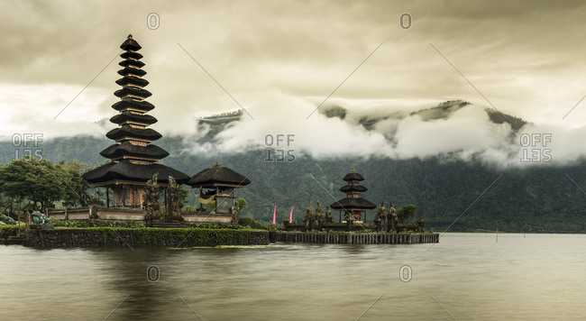 Mist covers the mountains around the Pura Ulun Danu Bratan temple, on a small island surrounded by a lake in Bali, Indonesia
