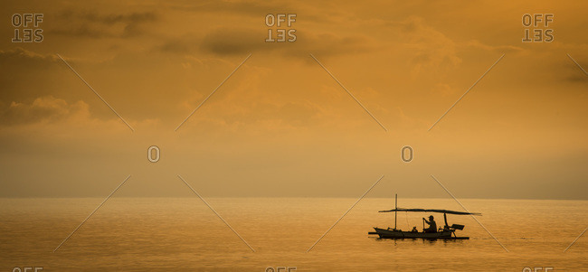 A fisherman heads out to sea at sunset near Permuteran, Bali, Indonesia