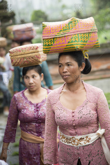 Bali, Indonesia - January 6, 2013: Women carry offerings in baskets on their heads at temple festival