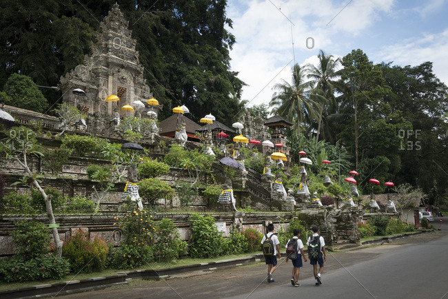School children walk past the Pura Kehen temple in Bali, Indonesia