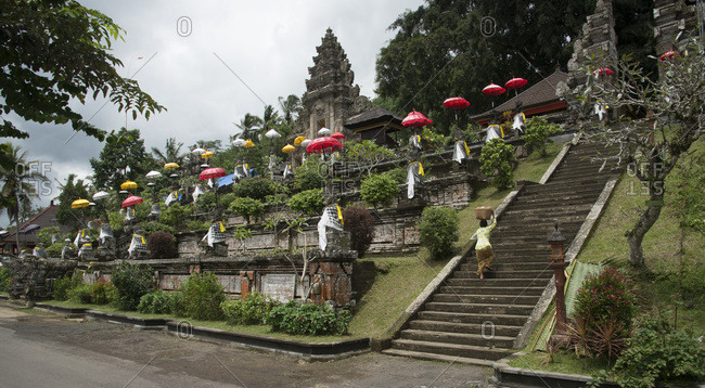 A woman with a basket on her head as she climbs the steps of the Pura Kehen temple in Bali, Indonesia