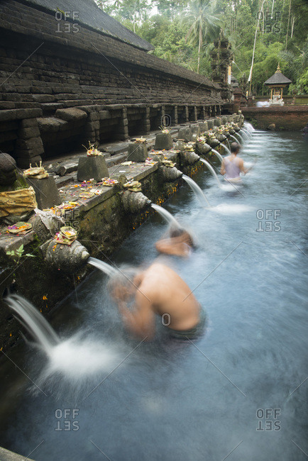 People washing themselves at the fountains of natural spring water, Tirta Empul Temple, Bali, Indonesia