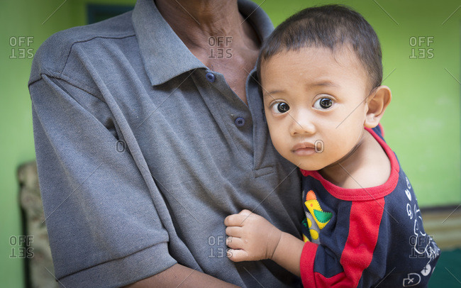 Bali, Indonesia - January 10, 2013: Portrait of a young boy with big eyes being held by his grandfather