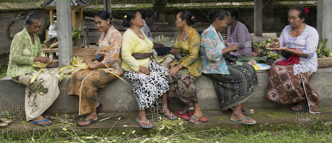 Bali, Indonesia - January 10, 2013: A group of women making offerings at a temple
