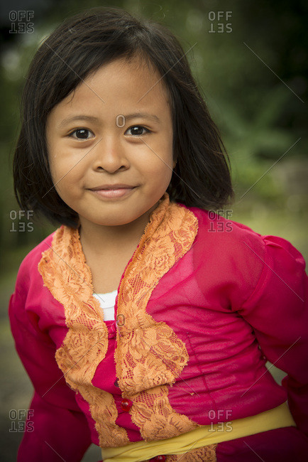 Bali, Indonesia - January 10, 2013: Portrait of a young girl wearing a red shirt
