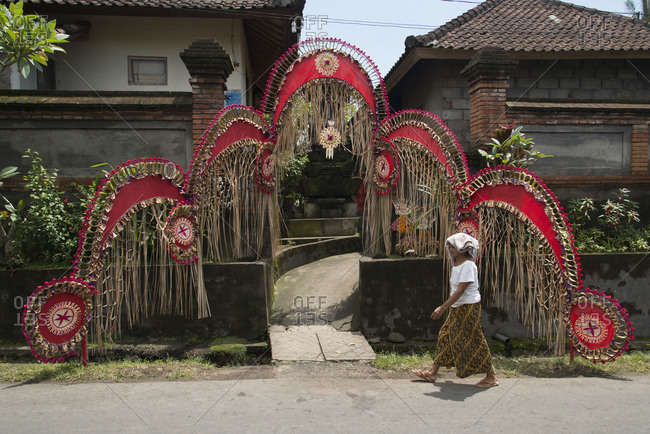 Ubud, Bali, Indonesia - January 11, 2013: A woman walks past a house decorated for a wedding