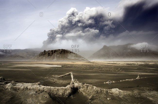 Landscape covered in volcanic ash and dust with the ash plume of the Eyjafjallajokull eruption in the distance, southern area, Iceland, Polar Regions