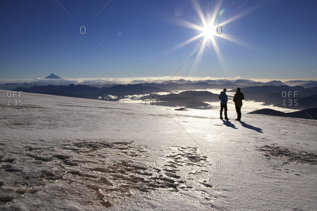 People watching a sunrise on a volcanic glacier, Huilo Huilo, Chile, South America