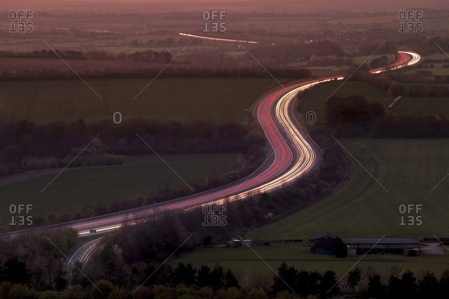 Telephoto aerial view of light trails at dusk on M40 motorway in The Chilterns, Oxfordshire, England, United Kingdom, Europe