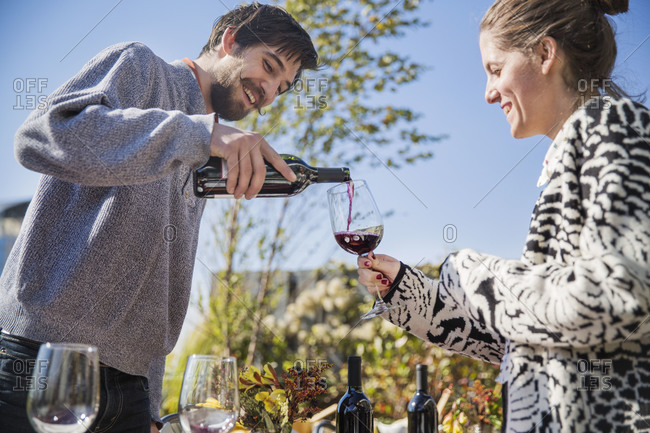 Young man pouring red wine to smiling woman