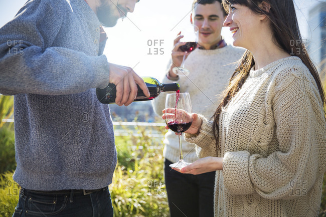 Young man pouring wine to smiling woman