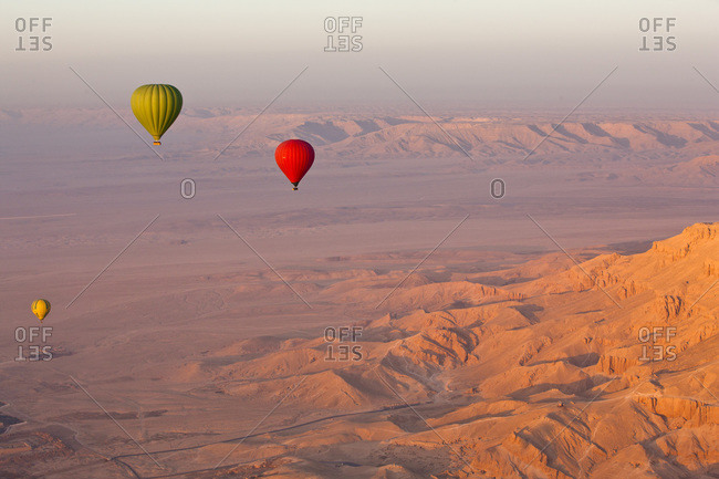 Hot air balloons suspended over the Theban hills of Luxor and the Valley of the Queens at sunrise, Thebes, Egypt, North Africa, Africa