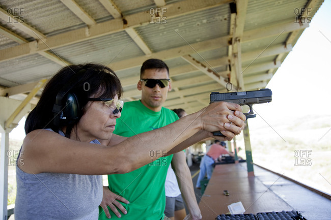 Hispanic woman learning to shoot a pistol with instructor
