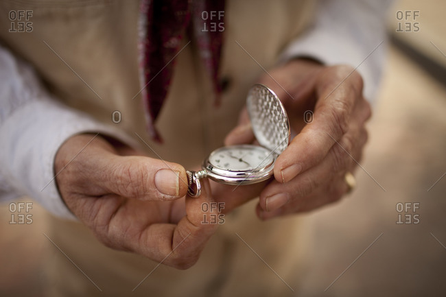 Hands of old cowboy with pocket watch
