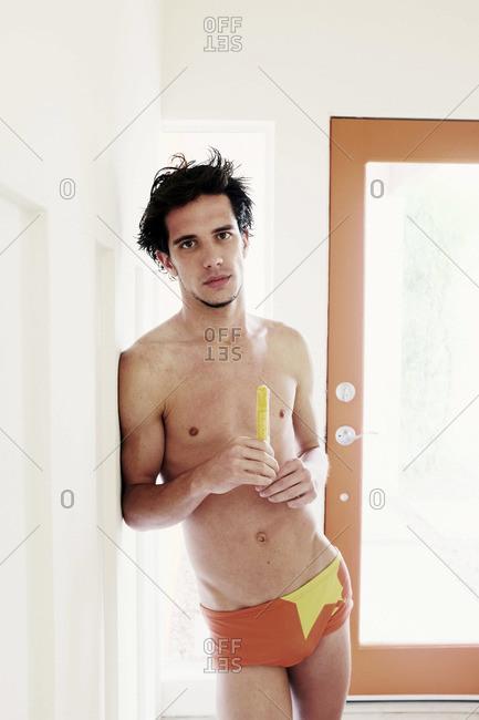 Man wearing swim briefs indoors