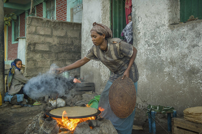Gonder, Ethiopia - January 19, 2008: Ethiopian woman making fire for cooking