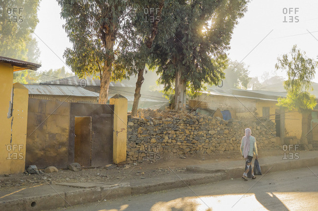 Ethiopian woman walking next to a collapsed wall