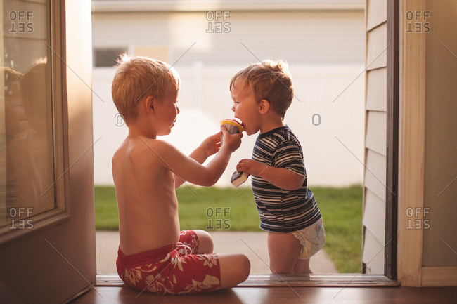 Male toddler and male youth share ice cream on a summer evening