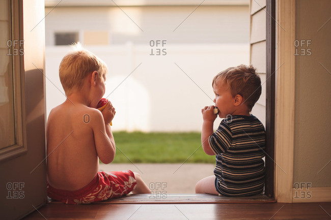 Male toddler and male youth having ice cream on a summer evening