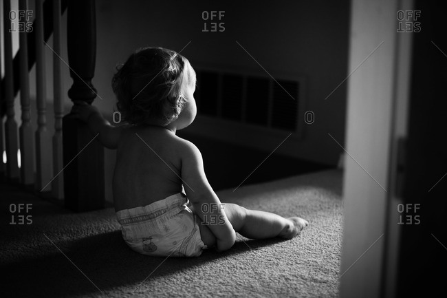 Male toddler in diaper stares into lighted doorway, seated and leaning on stair railing