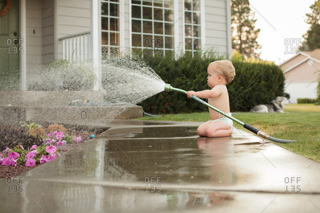 Male toddler watering the garden plants with water hose