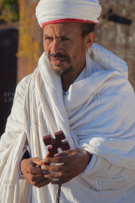 A priest outside one of the rock hewn churches of Lalibela, Ethiopia