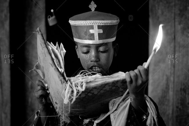 A boy reading from the scriptures in the Yemrehanna Krestos cave church near Lalibela, Ethiopia