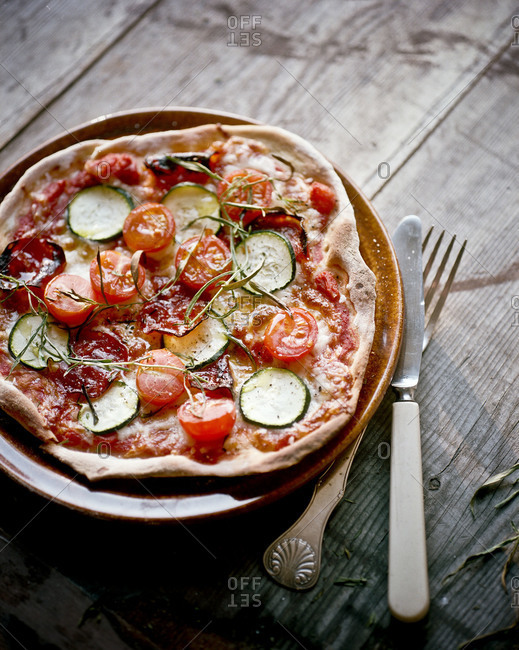 Homemade pizza with zucchini and tomato slices
