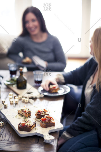 Two women enjoying crostini at a dinner party